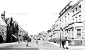 In this 1922 picture of Newmarket High Street, Cardigan Lodge is the first building on the right, with two people standing outside. It would have been the surgery of Dr Sidney Winslow Woollett at that time (see below), which is perhaps why the blinds are closed in the middle of the day? (see below or click image for more on the source and acknowledgements etc., ref. Image 1).