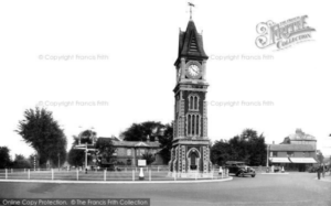 Heath Cottage is visible in the background of this old photograph from 1938 (just a couple of years after it ceased to be a surgery), the long building just to the left of the base of the clock tower, behind the roundabout. It's also of not that Cheveley House was gone by this stage - see the page on Cheveley House (see below or click image for more on the source and acknowledgements etc., ref. Image 1).