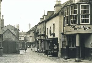 An old photograph of Drapery Row, obviously from well after the 17th century, but some elements of the scene perhaps giving an impression of what the street might have looked like in Gilman's time (see below or click image for source and acknowledgements etc., ref. Image 2).