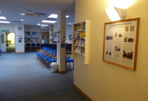 The main waiting room taken from the corridor leading to reception in 2013, with the newly installed history poster from the start of this research on the right (see below or click image for source and acknowledgements etc., ref. Image 2).